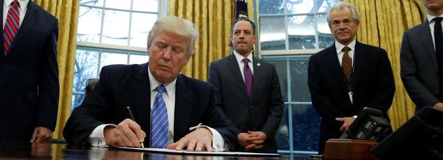 Donald Trump, entouré de Mike Pence, signe un décret dans le Bureau ovale, le 23 janvier 2017