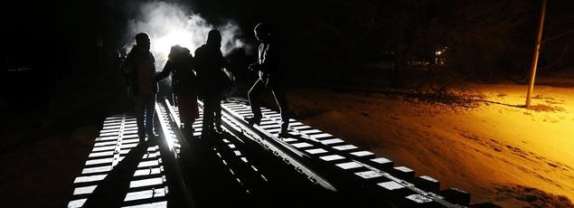 Des migrants somaliens traversent la frontière entre les États-Unis et le Canada en suivant une ligne de chemin de fer, à Emerson, dans l'État canadien de Manitoba, dimanche 26 février.