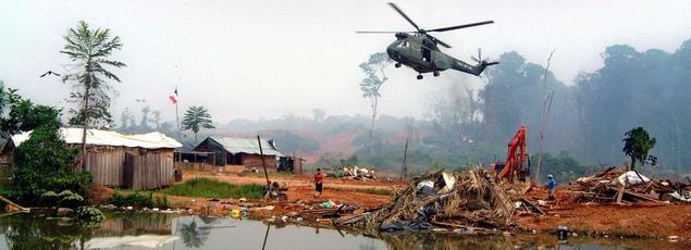 Un hélicoptère de la gendarmerie nationale se posant sur le village d'orpailleurs illégaux du site de Dorlin lors du démantèlement du village par les autorités françaises.