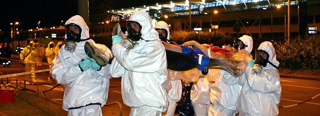 Des sauveteurs en tenue de protection chimique portent un blessé contaminé lors d'un exercice en 2005 de simulation d'attaque terroriste à l'aéroport de Lille.