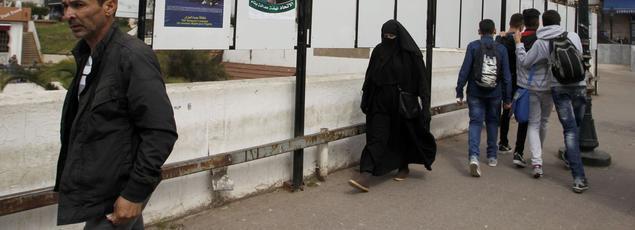 Une femme voilée passe devant des panneaux électoraux, le 9 avril, à Alger.
