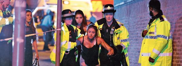 Des officiers de police aident une jeune fille blessée dans l'attentat, lundi soir à Manchester.