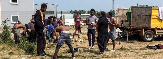 Des migrants font leur toilette, le 21 juin 2017 à Calais.