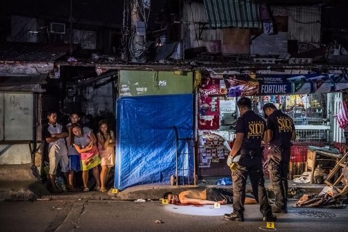 Manille, 2 octobre, 2016. Michael Araja (29 ans) était parmi les victimes abattues devant un kiosque «sari-sari» où, selon ses voisins, il s'était rendu pour acheter des cigarettes et une boisson pour sa femme. Deux hommes à moto ont tiré sur le groupe: un mode opératoire fréquemment utilisé, connu sous le nom de «virée en tandem». Sur le lieu du crime, des policiers relèvent des indices. © Daniel Berehulak pour <i>The New York Times</i>