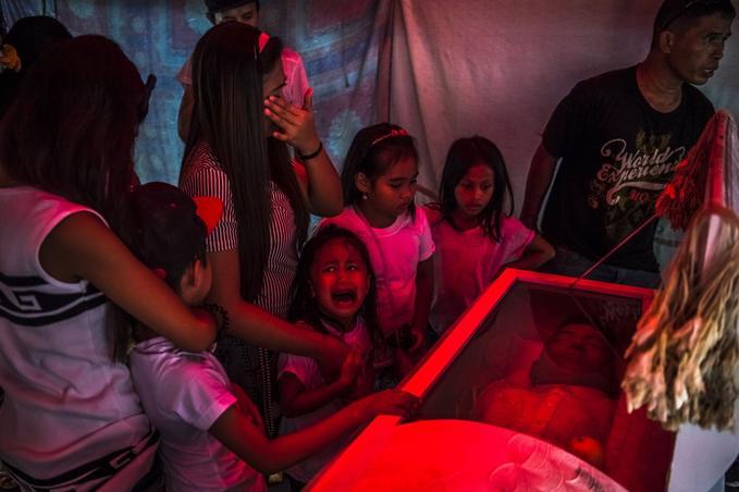 Manille, 10 octobre 2016. La souffrance de la petite Jimji (6 ans) qui hurle «Papa!» avant les obsèques de Jimboy Bolasa (25 ans). Des traces de torture et de blessures par balles étaient visibles sur le corps, retrouvé sous un pont. Selon la police, c'était un dealer ; selon ses proches, il avait répondu à l'appel du président Duterte et voulait suivre une cure de désintoxication. © Daniel Berehulak pour <i>The New York Times</i>