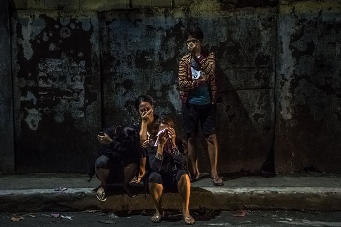 Manille, 3 octobre 2016. Des proches accablés à la vue des corps de Frederick Mafe et Arjay Lumbago, abattus en pleine rue. © Daniel Berehulak pour <i>The New York Times</i>