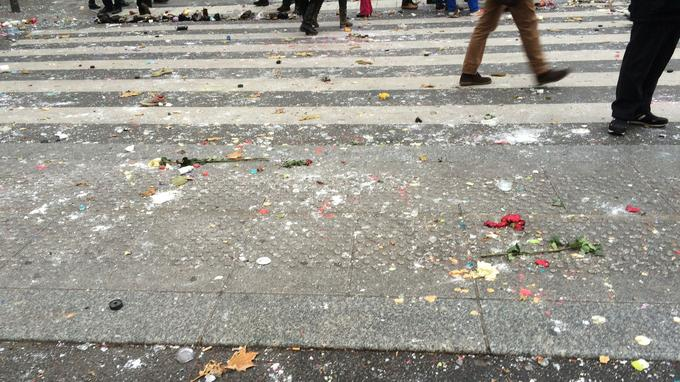 Le sol est jonché de débris de bougies et de fleurs provenant du mémorial et jetés sur la police.