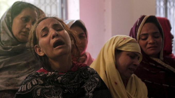 Des femmes pleurent la disparition d'un de leurs proches.
