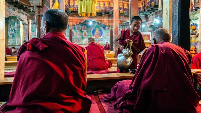 Pendant la première prière, au monastère de Thiksey. Un jeune moine sert du thé au lait de yak à ses maîtres. Le petit déjeuner n'interrompt pas la cérémonie: la vie du corps et la vie de l'âme ne font qu'un.