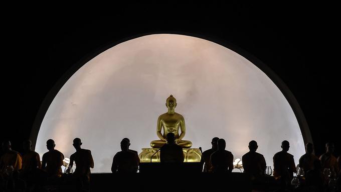 Des moines méditent devant une statue de Buddha dans la ville de Chiang Mai, en Thaïlande