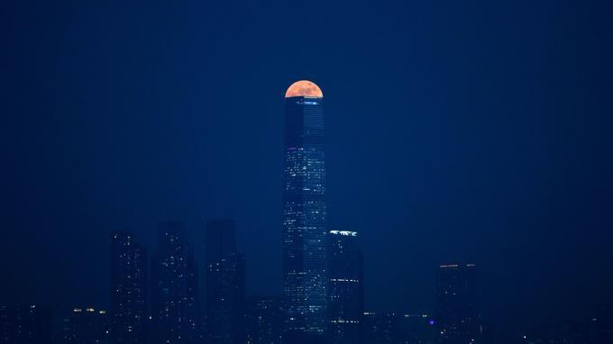 La super lune dans la continuité d'un gratte-ciel de Hong Kong