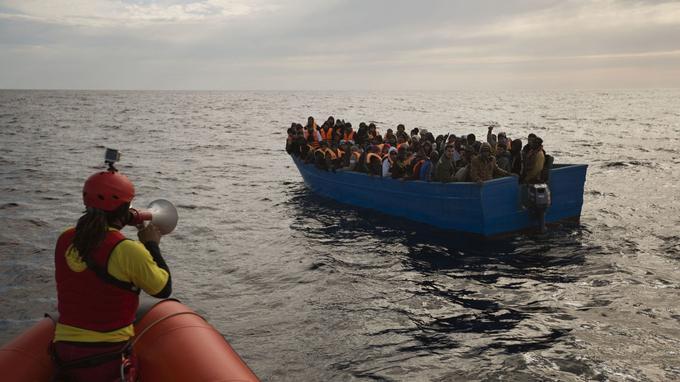 Un membre de l'ONG catalane Proactiva Open Arms, interpelle ici les migrants pour leur venir en aide.