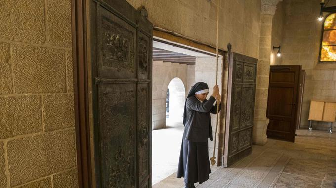 Une religieuse sonne les cloches pour la messe à l'Église de la multiplication des Pains.