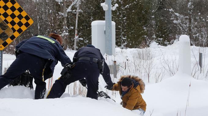Des agents de la GRC aident un homme qui explique être originaire de Mauritanie, dans la ville d'Hemmingford, au Québec, le 14 février.