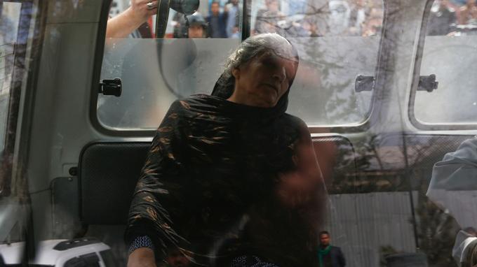 Une femme blessée reste à l'abri dans une ambulance.