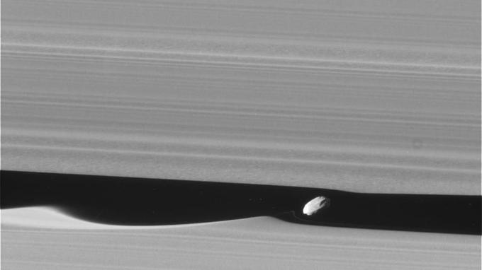 Le passage de la petite lune Daphnis laisse dans les anneaux de Saturne un sillage en forme de vague;