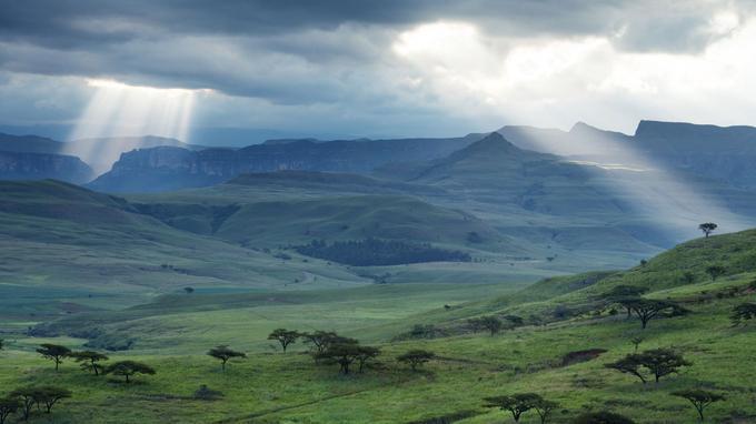 Fin de journée sur les Drakensberg. Les derniers rayons du soleil percent les nuages pour frôler les sommets de Champagne Castle et Monks Cowl.