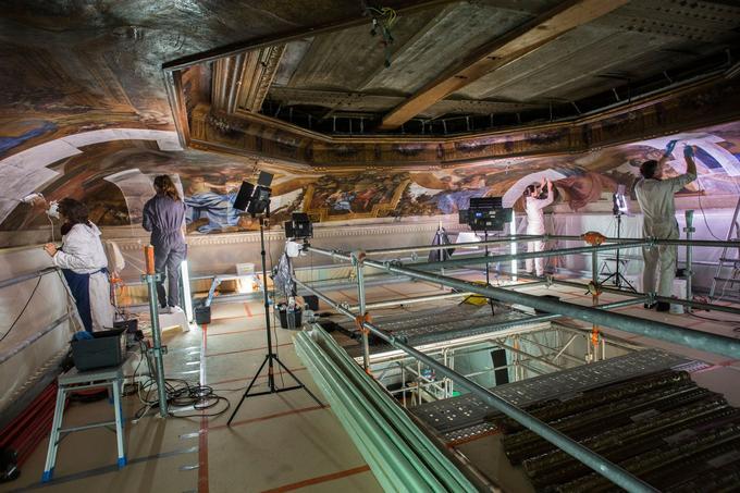 Pendant que l'œuvre principale est traitée en contrebas, les équipes s'emploient à redonner des couleurs aux peintures latérales.