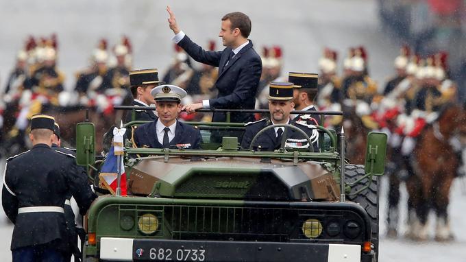 Emmanuel Macron remontant les Champs-Élysées dans un <i> command car</i>.