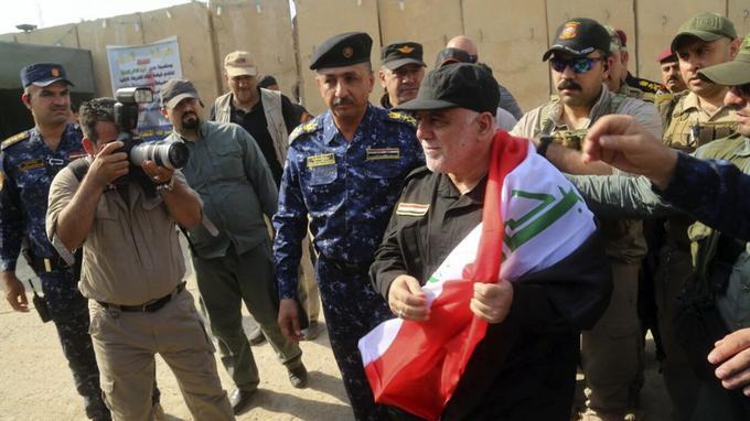Le premier ministre irakien Haider al-Abadi (au centre) félicite des officiers de l'armée et de la police, le 9 juillet 2017 à son arrivée à Mossoul.