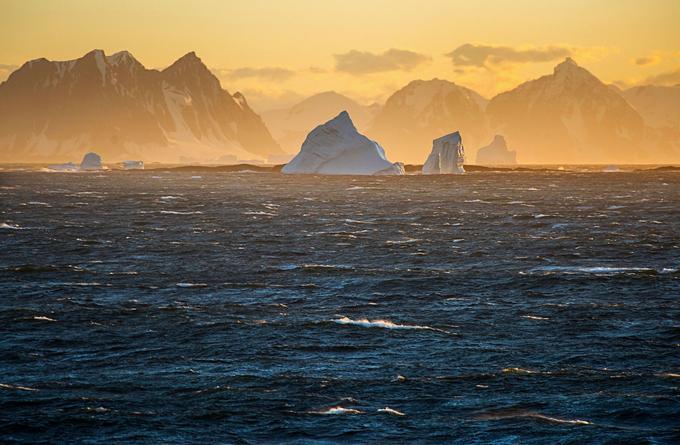 Les lumières australes marquent à jamais ceux qui les contemplent. À l'aube, elles nimbent montagnes et icebergs d'un halo rose orangé.