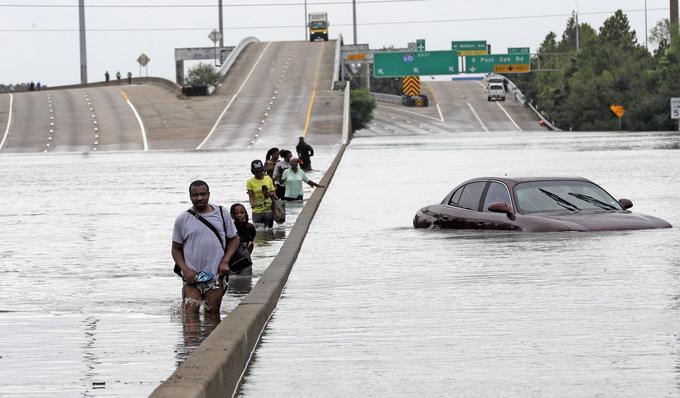 Certains habitants ont évacué la ville de Houston le 27 août en traversant une route inondée.