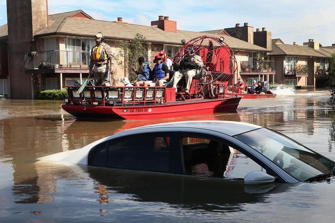 Les secouristes et des volontaires évacuent les habitants d'un quartier de Houston.