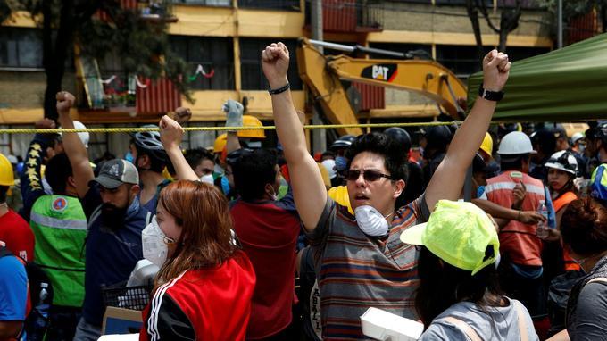 Les Mexicains lèvent les poings en l'air pour demander le silence et permettre aux secouristes de retrouver plus facilement les survivants, le lendemain du séïsme qui a frappé le Mexique le 19 septembre.