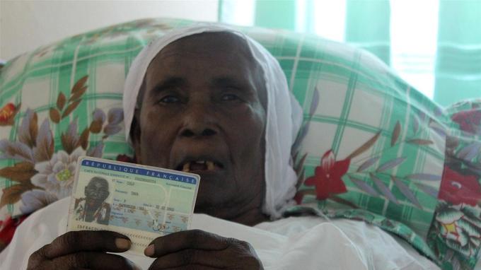 Tava Colo, alitée chez l'une de ses petites filles dans son village natal de Passamainty (Mamoudzou, Mayotte). La doyenne tient dans les mains sa carte d'identité, selon laquelle elle est née le 22 décembre 1902.