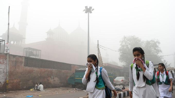 Des étudiantes indiennes se couvrent la bouche pour ne pas respirer le smog épais, le 8 novembre dernier. Depuis mardi, l'ensemble des établissements scolaires ont été fermés pour protéger les poumons des enfants.