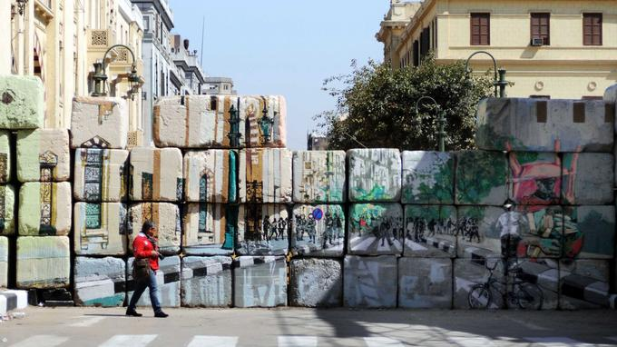 Un mur érigé par les autorités égyptiennes, Rue Sheikh Rihan en mars 2012. Le trompe-l'oeil est régulièrement utilisé pour imiter la destruction d'un mur empêchant la libre-circulation.