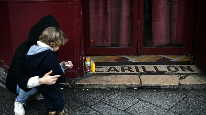 Une femme et son fils allument des bougies en hommage aux victimes des attentats, devant le bar Le Carillon, le 13 novembre 2016.