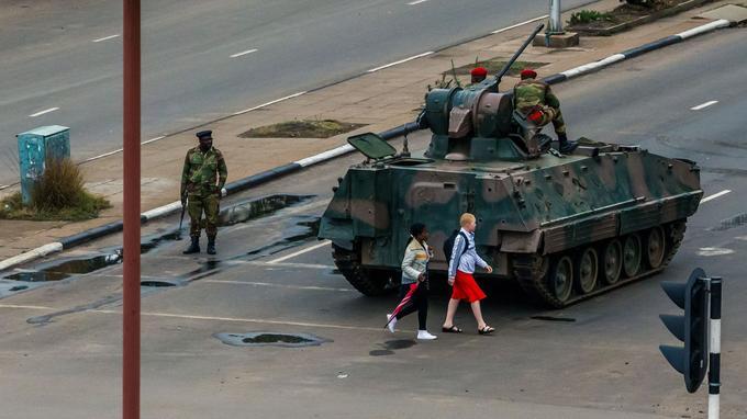 Des jeunes filles passent devant un char stationné à une intersection de rues, dans la capitale zimbabwéenne Harare, mercredi.