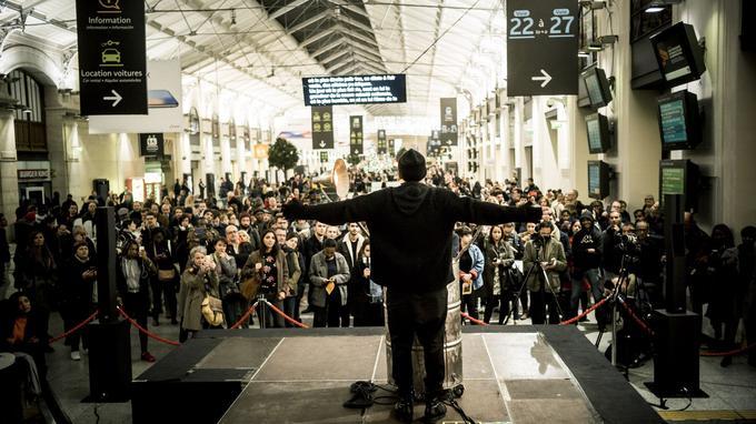Peu avant la fin de la représentation, plusieurs centaines de personnes sont massées au premier étage de la gare Saint-Lazare pour écouter le rappeur prononcer ces hymnes sur la paix..