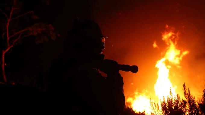 Un pompier travaille au sommet d'une colline alors que le «Lilac fire» brûle à travers la zone de Bonsall, en Californie.