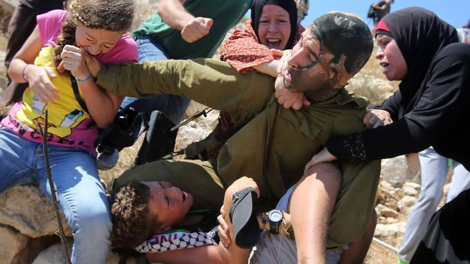Ahed Tamimi tente de faire lâcher prise en mordant le soldat israélien qui tente d'arrêter son petit frère.