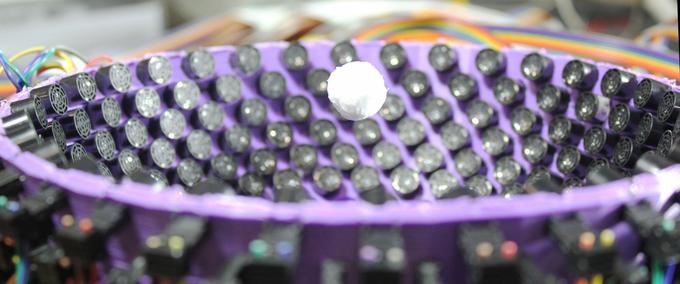 Une balle en polystyrène de 1,6 cm maintenue en position au dessus d'une série de haut-parleurs.