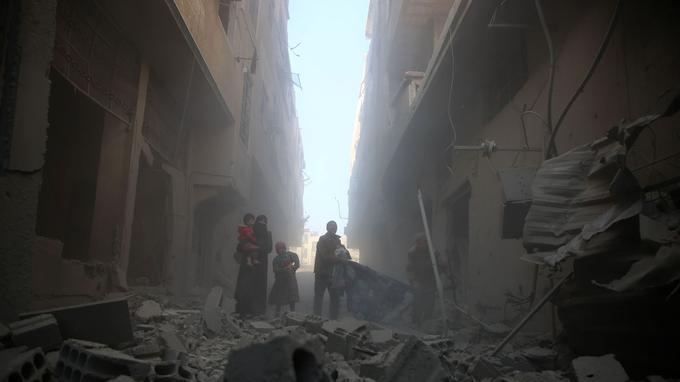 Une famille traverse les décombres provoqués par des frappes aériennes à la Ghouta.