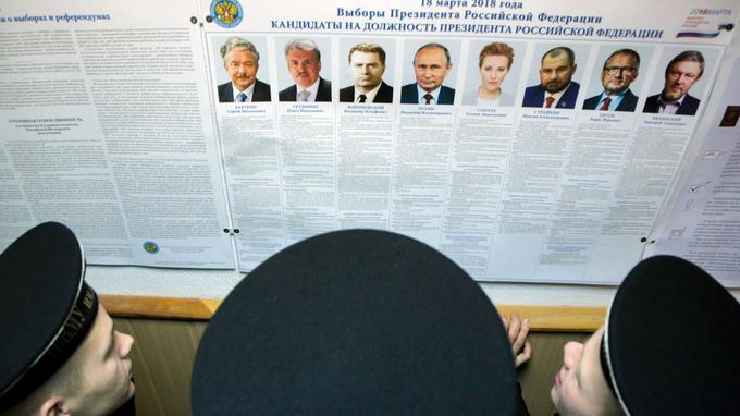 Des marins regardent la liste des 8 candidats dans une base de Sebastopol en Crimée.