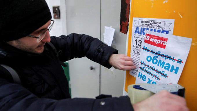 Un partisan d'Alexeï Navalny collant une affiche qui appelle au boycott de l'élection présidentielle du dimanche 18 mars