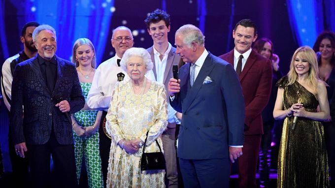 Elizabeth II sur la scène du Royal Albert Hall, à la fin du concert organisé pour ses 92 ans samedi 21 avril 2018. Elle est entourée de son fils le prince Charles, ainsi que des artistes du spectacle comme Tom Jones (à sa droite) et Kylie Minogue (à sa gauche).