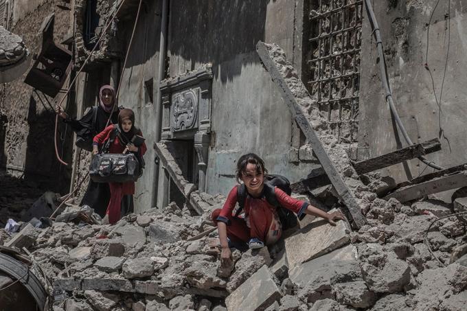 Mossoul, Irak, le 29 juin 2017. L'armée, la police fédérale et les forces spéciales des services du contre-terrorisme irakien entament une nouvelle avance conjuguée au centre de la vieille ville de Mossoul, dont fait partie le secteur de la mosquée Al-Nouri. L'avance se fait de maison en maison avec l'aide des frappes aériennes de la coalition. Ici des civils restés sortent de leurs maisons dans les décombres des bâtiments détruits par les bombardements. © Laurent Van der Stockt pour <i>Le Monde </i>/ Getty Images Reportage