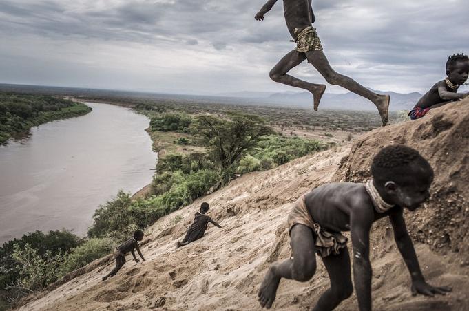 Des enfants jouent sur les rives de l'Omo qui s'écoule du nord au sud de l'Ethiopie. Le cours de la rivière et sa vallée sont menacés par le barrage Le Gibe III, plus haut barrage hydroélectrique d'Afrique avec ses 243 mètres.© Fausto Podavini