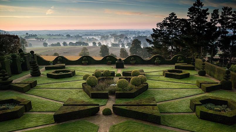Le panorama à couper le souffle du jardin contemporain d'inspiration classique avec, en toile de fond, la campagne bretonne encore embrumée.