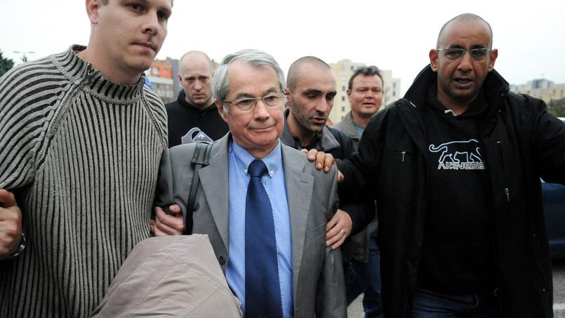 Le directeur des ressources humaines (DRH) de Caterpillar, Maurice Petit, est escorté à sa sortie de l'usine de Grenoble, où il était retenu, le 31 mars 2009. Relâché pour des raisons médicales, quatre autres dirigeants resteront quant à eux retenus pendant 24 heures.
