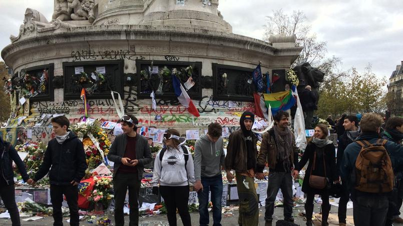 Des militants forment une chaîne humaine pour empêcher certains manifestants de s'emparer des bougies du mémorial pour les jeter sur les CRS.