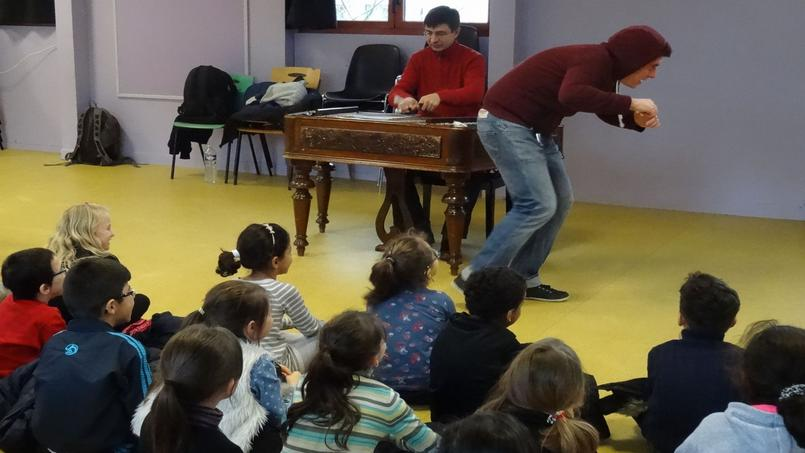 Florian joue une scène en musique devant les enfants enjoués