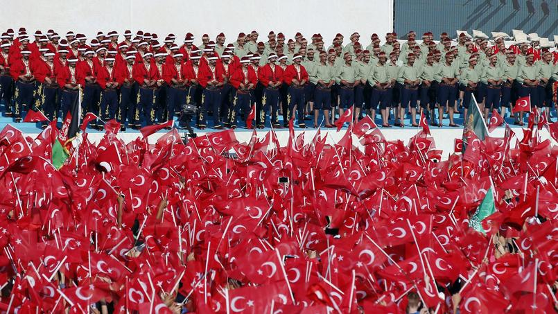 La foule agite des drapeaux devant des figurant habillés en costume de soldats ottomans.