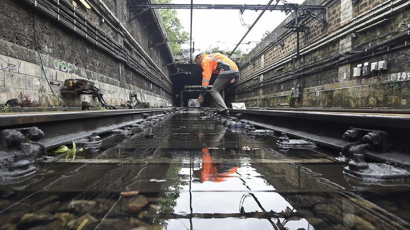 Un ouvrier réparant les dégâts causés par les inondations sur la ligne du RER C.