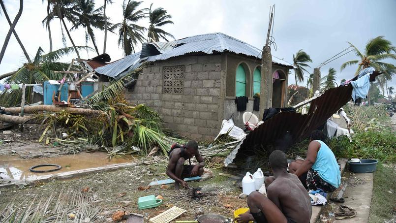 Une famille prépare sa nourriture devant une maison détruite à Croix Marche-a-Terre, dans le Sud-Ouest de l'île, jeudi.